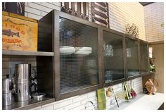 Vintage style glass wall kitchen cabinets with wire framed glass inserts. Very industrial with metal shelving against metro style wall. Industrial style kitchen by Scavolini & Diesel photographed by Moregeous at KBB 2016 http://moregeous.com/2016/03/07/kbb-2016-a-seriously-on-trend-industrial-kitchen/