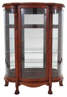 A substantial bow-front glass curio case in oak on carved claw feet. Carved  detailing on the upper portion of