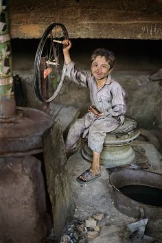 Photo and caption by Steve McCurry ~ Afganistan ~ It is estimated that at least 30% of children from five to fourteen work to help their families survive.  Many weave rugs and work at factories making bricks.