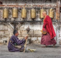 Begger and Monk by Jim Caldwell.  Photographed during a religious holiday in Lhasa, Tibet next to the Potola Palace.