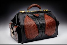 """Some lovely modern day versions are being made.     This Doctor bag features beautiful alligator hide appliqued into the front, back and side panels. The wet formed pockets on each end have carved elk horn closures. Handles are laminated leather formed, wrapped and stitched by hand. All doctor bags are one of a kind. 13"""" x 22"""" x 11"""" Made by Edgar Leather USA"""