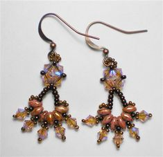 Free Superduo earring pattern - 1  Materials:   2.5 x 5 mm Superduos (P65491, opaque rose/gold topaz)     4 mm bicone crystals (Swarovski, vintage rose AB2X)     11/0 seed beads (Miyuki 11-460, metallic dark raspberry)     15/0 seed beads (Miyuki 15-457L, metallic light bronze)     pair of earring findings     Fireline 6 lb. test     Beading needles, #11 or 12.