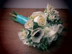 Bridal bouquet of white roses, anemones, ranunculus, bouvardia and eucalyptus with aqua accents by Apple Blossom