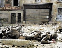 A Medic attends to a wounded Captain of the US 317th Infantry Regiment, 80th Division, whilst under fire in Rue Maréchal Joffre, Pont-à-Mousson on the Moselle River, France. Early September 1944.