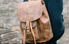 Our men's leather rucksack is compact but mighty. This classic style bag is met with our rugged distressed leather for a cool and hip look. Get our leather backpack that was inspired by explorers discovering foreign lands. #backpack #vintage #adventure #vintagegift #giftideas