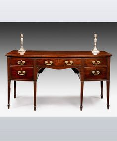 A Hepplewhite period mahogany bowfront sideboard with shaped apron; raised on square taper legs.  Circa 1780