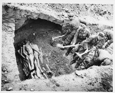 "German prisoners uncover a mass grave holding victims of Kaufering Camp III.    The original caption reads, ""Atrocity Story. German murder camp known as Lager #3. German prisoners uncover a mass grave used for the disposition of bodies. The [hole] is approx. 12' X 50' and bodies are stacked 5 high. Death was traced to various reasons. Some were given a poison hypodermic in the wrist, others had died from starvation or typhus. This pit, one of many, was estimated to hold 1,000 bodies."""