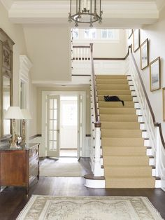 Traditional foyer with golden leaf frames, antique chest and French shutters. Phoebe Howard.