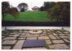 """The Kennedy Gravesites in Arlington Nat. Cemetery postcard: The eternal flame, first lighted on Nov. 25, 1963, burns continuously over the grave of JFK, the 35th president. Speaking at Arlington House in the cemetery on Nov. 11, 1963, Kennedy prophetically said, """"I could stay here forever."""" Nearby a simple white wooden cross marks the site of Robert Kennedy's grave."""