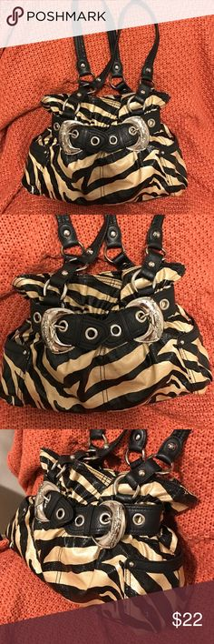 Kathy Van Zeeland black/gold zebra purse Beautiful Kathy Van Zeeland black/gold purse with silver buckles. The outside is shiny patent. It has side pockets and a zipper compartment in the back. There a few ink stains on the inside but otherwise very clean. This is one fabulous purse ! Kathy Van Zeeland Bags
