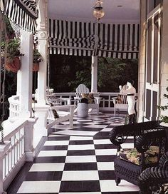 Gorgeous porch!  It has a kind of early 1900's feel with the checkered floor and striped curtains around the porch
