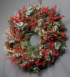 Classic Red Berry Wreath - This traditional red berry wreath uses ilex berries, pine cones, pussy willow and eucalyptus. From £90 wildatheart.com