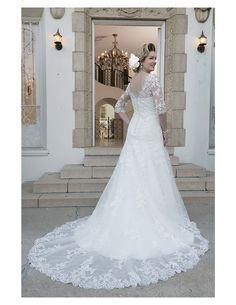 Elegant v back and sheer train on this lace-sleeved beauty available at Spotlight! #SpotlightBridal