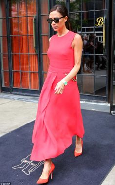 Lady in red: Victoria Beckham left her hotel in New York City in a bold red midi-length dress with a knee length slash and gold waist chain http://dailym.ai/1ilLHwG