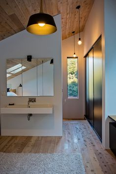 At the top of the stairs in this modern house is a built-in closet and a small vanity area. #ModernInteriorDesign #WoodCeiling #SlopedCeiling