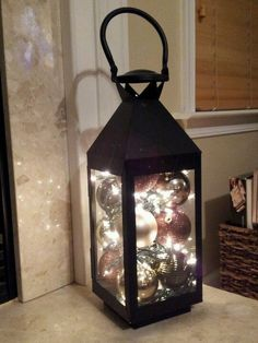 Ornament Lantern --- Instead of sticking a generic candle inside of a lantern, enclose a handful of ornaments and battery-operated Christmas lights for a more eclectic look. I'd love to place these by my front door!