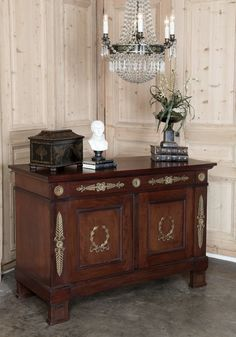 Antique Empire Style Mahogany Buffet. Considered by many to be the most formal of French styles, the Empire style dawned during the reign of Napoleon Bonaparte, and was revived when his nephew assumed power during the Second Empire. This example, hand-crafted from exotic imported mahogany, exhibits classic Empire motifs in the cast bronze ormolu mounts with styling influenced by the ancient Egyptians of whom Napoleon was so enamoured. Spacious interior affords excellent storage in style!