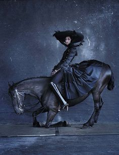 The midnight hour. Dramatic, moody photo with midnight-blue clad woman astride a dark horse kneeling. (Leah Cultice)