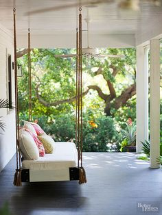 Although furniture is a quick fix, a swinging patio bed is a simple, charming DIY solution to relax-worthy seating. Adapt a platform or bench to hold a cushion and a back support. Hooks should be attached to beams, not the ceiling itself.  /