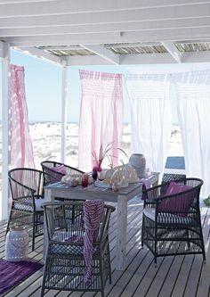 Schön!      Mitten in den Dünen Deutschlands. Abgeschirmt und doch frei. Dieser offene Pavillon in Magenta-Weiß schirmt die pralle Sonne ab, ohne sie auszugrenzen. Edle Stühle in Schwarz zeichnen sich ebenfalls durch ihr luftdurchlässiges Design aus. Statt einheitlicher Dekoration überzeugt jede Sitzmöglichkeit durch magentafarbene Individualität. Leichte Rüschenvorhänge in dezenter Rosa-Weiß-Kombination plustern sich auf. Ein Ort vom Winde befreit.