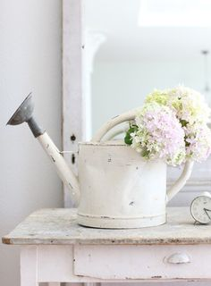 white watering can and sweet spring flowers