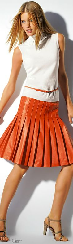 Madeleine. Orange leather: pleated skirt & belt, white turtleneck top, sandals. I don't normally go for leather, but I like this.