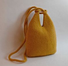 This simple purse is designed like a small tote with a sliding infinity loop for closure. It is knit in the round in one piece, then felted in a washing machine (complete instructions are provided for felting). It can be made to either cross body or shoulder bag length- both look nice.