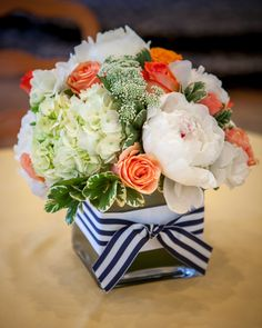 Coral and white centerpiece with a touch of navy blue. I love beautiful flowers.