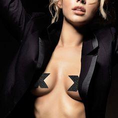 CUBREPEZONES ADHESIVOS CRUZ NEGRO CON BRILLO COLECCIÓN FLASH DE BIJOUX INDISCRETS. ¡Superwoman! Revela tu verdadera identidad y hazle sucumbir con el poder de tus súper encantos con FLASH. Reutilizables, se adaptan a todo tipo de pecho. Ideales para atraer todas las miradas en tus looks con transparencias, tus vestidos abiertos en la espalda o tus escotes de vértigo. ¡Atrévete a dejar el sujetador en casa! #pezoneras #cubrepezones #adhesivos #BijouxIndiscrets