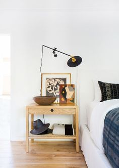 A serene, calming, and modern bedside collection with small art pieces and wooden bowl