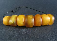 7 ANTIQUE NATURAL AMBER beads. MOROCCO  Seven antique natural amber beads from Morocco. Wide barrels with some bveled ends. Nice tones and transparencies. Small size.    I'm sorry, I fortgot the picture with the coin. Please, see measures.    Weared. Good condition.  Highly collectible and useful as jewelry supplies.    Central bead measures: 13 x 19,2 mm.  Weigth: 15,8 gr.  Price: $ 189