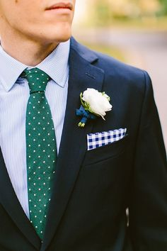 Blue/Green style; Navy suit, blue striped shirt, forest green polka dot tie, royal blue checkered pocket square and white rose buttonhole.