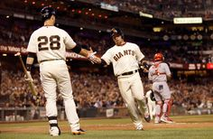 Juan Perez #2 of the San Francisco Giants is congratulated by Buster Posey #28 after he scored on a hit by Hunter Pence #8 in the fifth inni...