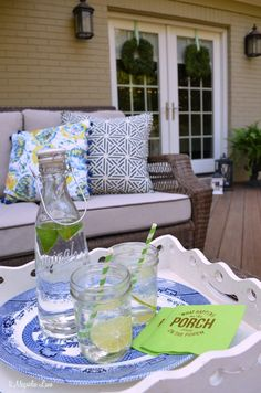 The deck is the perfect place to relax during the summer.  We decorated this porch with colorful outdoor throw pillows, twinkling lights, lots of greenery--including ferns and boxwood wreaths--and of course a few icy libations.  Even when the temperature is sky-high, this space is so inviting! {sponsored by HomeGoods}
