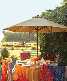 A giant umbrella shields party guests from the blazing afternoon sun, and hanging lanterns will illuminate the table come nightfall. Mix citronella candles with other colorful tea lights to keep away pests, and offer diners light cotton shawls to ward off a chill in the evening.   - CountryLiving.com