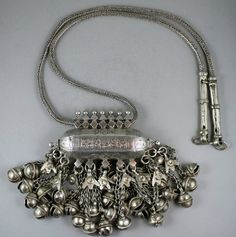 Yemeni Amulet from the Hadramaut  This is a heavy silver wedding necklace from the Hadramaut, probably from Wadi Daw'an. The cucumber-shaped amulet has finely engraved floral decoration, with granulated pyramid finials on either side and forming the bails. Beneath it hangs profuse bells, none missing or replaced. Hands of Fatimah hang at the front of each row of bells.