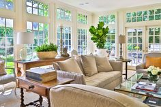 Vintage garden accents combine with antiques and casual, yet elegant slipcovered furnishings and other textural upholstery in the home's family room. Upholstery from Hien Lam; French library table from MAI. A sea grass rug adds to the room's rich organic feel.