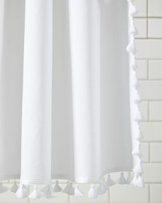 It's the little details that we love the most. Pure white cotton canvas gets a trim of playful tassels along the sides and bottom of each curtain in a bright, contrasting color.