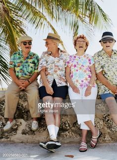 Stock Photo : Group of four senior people sitting on wall outdoors, laughing