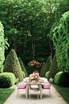 Clipped hedges, ghost chairs, topiary centerpiece