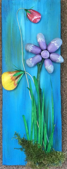 Acrylic painted pebbles mounted on a reclaimed wood as a backdrop.
