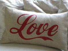 """Burlap pillow cover with the word Love hand printed in red across the front. Coca-Cola style font - very cool.    Envelope enclosure at back.    Fits pillow (20"""" x 12"""") 50cm x 30cm which is not included.    Spot clean only. Burlap cannot be washed."""