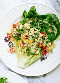 Beautiful Greek salad made with wedges of romaine lettuce, fresh tomatoes and olives piled on top, and a lemon tahini dressing. Easily vegan.