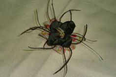 flor confeccionada en raso estampado y raso verde botella, detalle de plumas alrededor de la flor