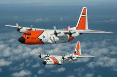An HC-130J crew flies in formation with a legacy HC-130H repainted in the original Coast Guard livery.