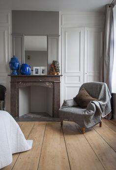 Chambre dans une maison du 18ème située dans le Vieux Lille, fauteuil gris, cheminée en marbre, poterie bleu klein, parquet ancien, moulures, statuette
