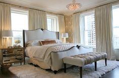 Summer Thornton Design -Beautiful bedroom with custom white linen bed with black trim, tufted bench, white flokati rug, mirrored nightstands with gold trim, off white pinch-pleat silk curtains window panels and Regina Andrew Alabaster Quatrefoil Lamps - Large