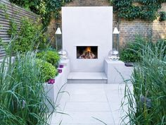 The Old World feel of the brick privacy wall perfectly juxtaposes the stark modern lines of the patio's fireplace. The white fireplace surround allows the fire to be the focal point. Our Favorite Designer Outdoor Rooms | Outdoor Spaces - Patio Ideas, Decks & Gardens | HGTV