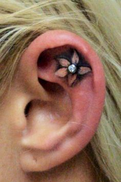Small flower tattoo in ear with diamond earring accent