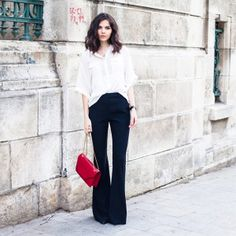 Doinaciobanu wears a relaxed white blouse with flared pants and a bright red accent bag // #Fashion #StreetStyle